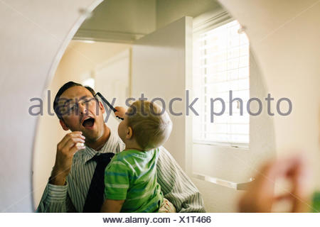 Father holding young son, son trying to comb father's hair, reflected in mirror - Stock Photo