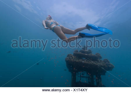 Woman snorkeling by a sunken temple, Bali, Indonesia - Stock Photo