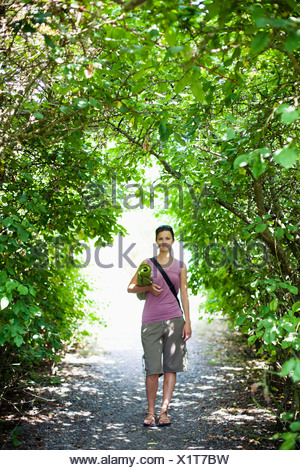 A young woman stands in an arch of greenery while holding her yoga mat. - Stock Photo