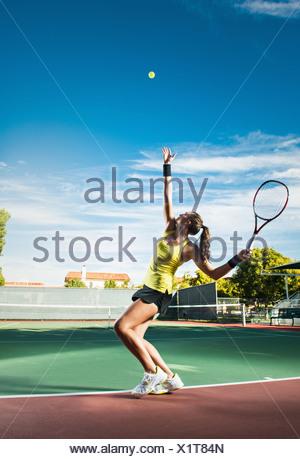 Female tennis player hitting ball - Stock Photo