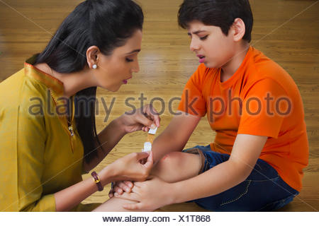 Mother putting bandage on sons wound - Stock Photo