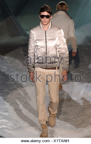 Iceberg Menswear Milan A W Brunette male wearing a taupe puffy satin motorcycle jacket khaki trousers, matching ankle boots and - Stock Photo