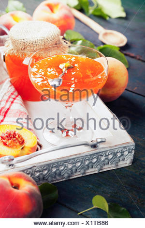 Peach jam with fresh peaches on rustic table. Homemade bio food concept - Stock Photo