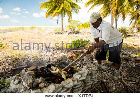Cooking lunch on coconut frond fire, Kiribati - Stock Photo