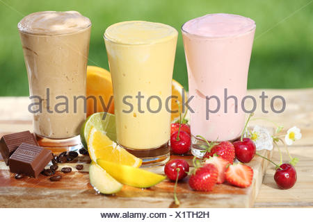 Three delicious smoothies with yoghurt or ice cream blend, two made with fruit and one of chocolate, together with various fresh tropical fruit on a garden table - Stock Photo