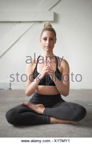 Mid adult woman meditating lotus pose in yoga studio, Munich, Bavaria, Germany - Stock Photo