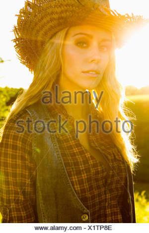 Woman wearing vest and straw hat - Stock Photo