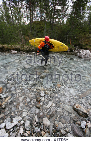 A man carrying a kayak makes his way through a shallow rocky area in the Brandseht River in the western part of Norway. - Stock Photo