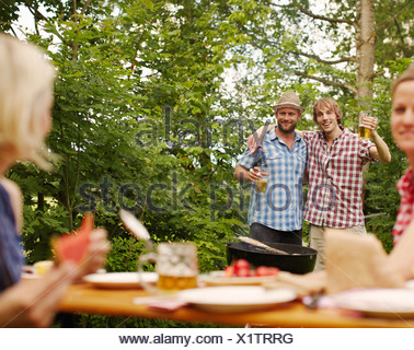 Friends drinking beer outdoors - Stock Photo