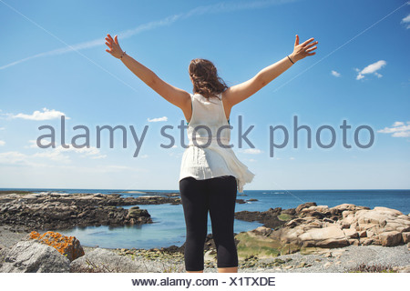 Rear view of young woman at the rocky coastal beach in Biddeford, Maine, USA - Stock Photo