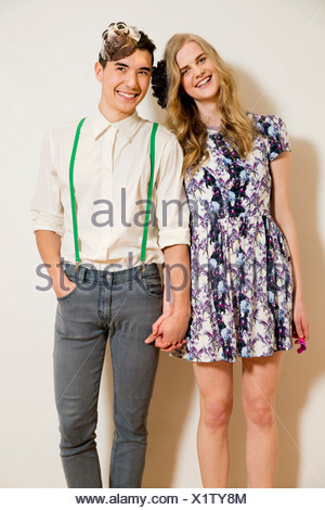 Portrait of young couple holding hands - Stock Photo