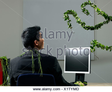 Man by desk beeing attacked by plants - Stock Photo