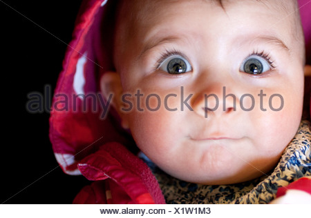 Close up of baby girl's surprised face - Stock Photo