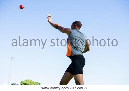 Athlete throwing shot put ball - Stock Photo