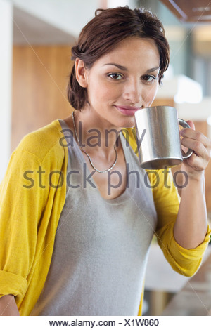 Woman drinking herbal tea in the kitchen - Stock Photo