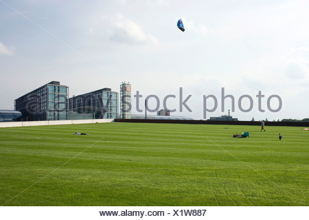 People on a meadow flying kites in front of the central station of Berlin, Germany, Europe - Stock Photo