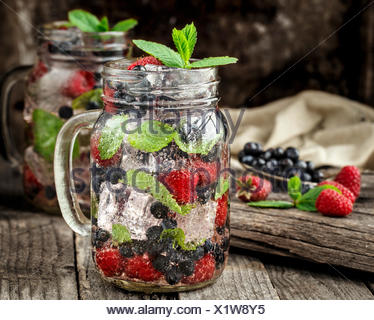 Detox drink with fresh berries, mint and ice in glass jars on wooden background - Stock Photo