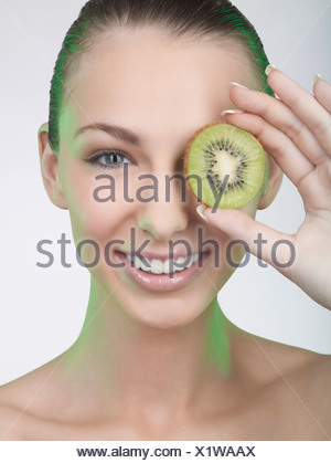 A woman holding a slice of kiwi fruit in front of her eye - Stock Photo