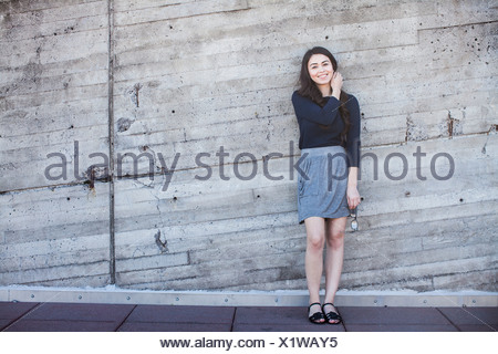 Young woman standing, leaning against wall
