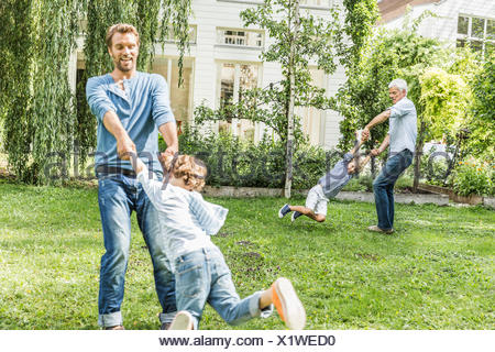 Mid adult man with father playing swings with sons in garden - Stock Photo