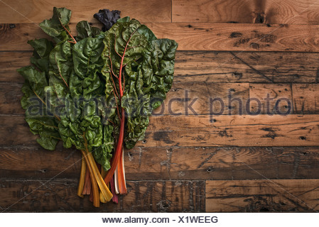group of red and orange chard leaves with bright coloured stems Organic vegetables freshly picked and placed on a wooden board - Stock Photo