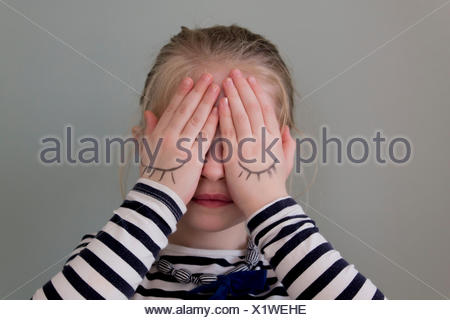 Girl covering her eyes with hands that have eyes drawn on them - Stock Photo