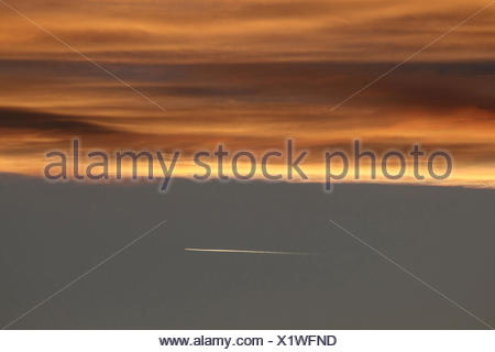 sunset with condensation trail of an airplane, Germany - Stock Photo