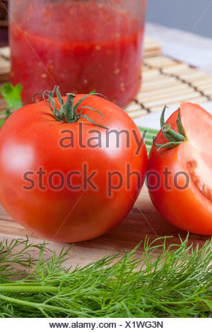 Red tomato on a table with a jar - Stock Photo