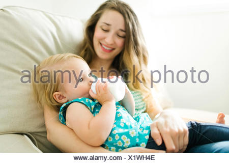 Mother feeding baby girl (12-17 months) in living room - Stock Photo