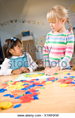 Two preschool children working together on colorful shape puzzle - Stock Photo