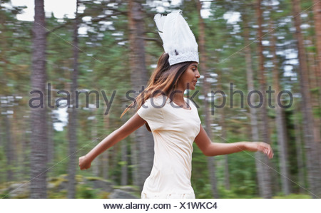 Teenage girl wearing white hat running in forest - Stock Photo