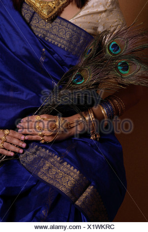 Torso of Indian woman holding peacock feathers - Stock Photo