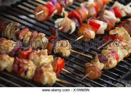 meat skewers and vegetables on the grill - Stock Photo