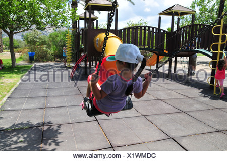Israel, Haifa, The Kishon Park on the banks of the Kishon river Girl plays in a public playground - model release available - Stock Photo