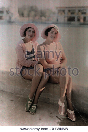 Two girls in bathing suits sit on a concrete ledge. - Stock Photo