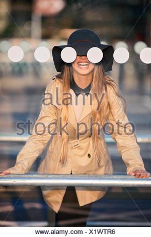 Smiling girl (12-13 )in hat seeing through bus stop