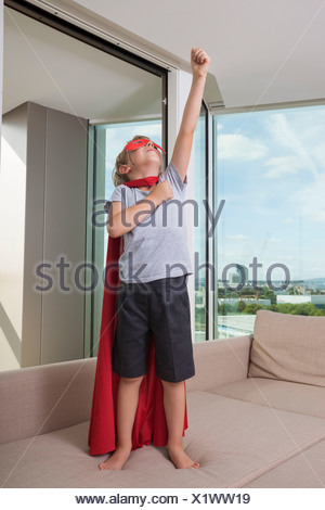 Boy in pretending to be super hero on sofa bed at home - Stock Photo