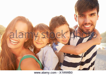Parents Giving Children Piggybacks On Summer Holiday - Stock Photo