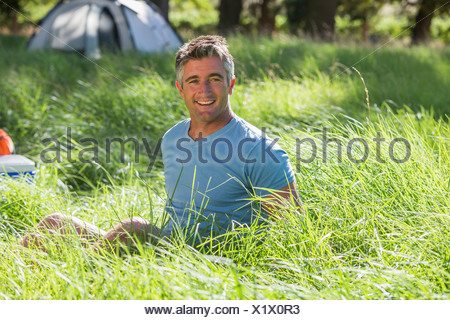 Man Relaxing On Camping Trip In Countryside - Stock Photo