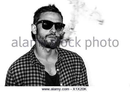 man smoking cigarette black and white portrait - Stock Photo