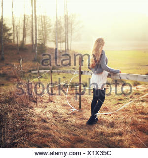 Woman standing by fence in rural landscape looking at the view, Norway - Stock Photo