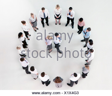 Businessman and businesswoman standing back to back in circle formed by co-workers - Stock Photo