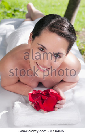 Portrait of a woman lying on a massage table holding rose petals - Stock Photo