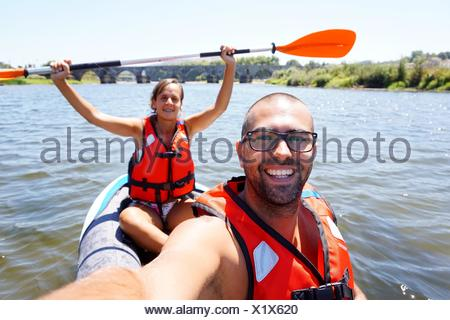Portrait Of Happy Young Man And Woman Kayaking On River - Stock Photo