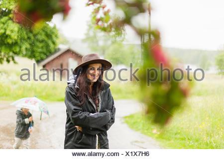 Sweden, Varmland, Filipstad, Gasborn, Horrsjon, Portrait of woman standing in rain - Stock Photo