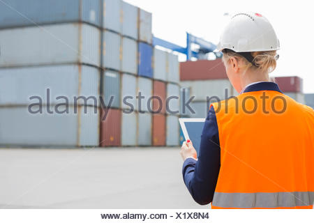 Rear view of female engineer using digital tablet in shipping yard - Stock Photo