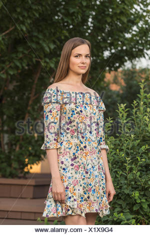 Portrait of beautiful young woman in dress outdoors - Stock Photo