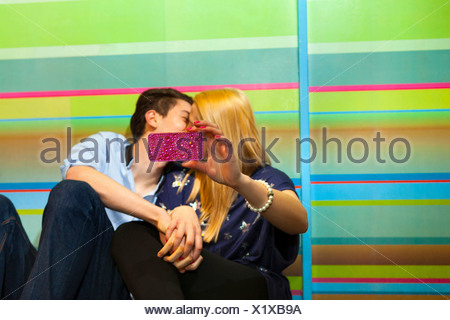 Young couple taking self portrait photograph of kiss - Stock Photo