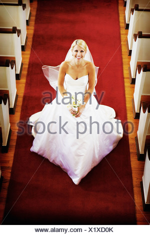Bride holding wedding bouquet whilst walking down church aisle - Stock Photo