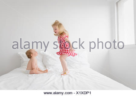 0f7f3b1f0a8 Smiling blond girl wearing red and white checkered dress jumping on bed